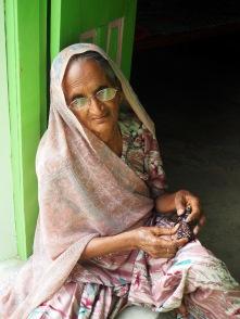 Lady at Kala Raksha sewing in the winter sunshine