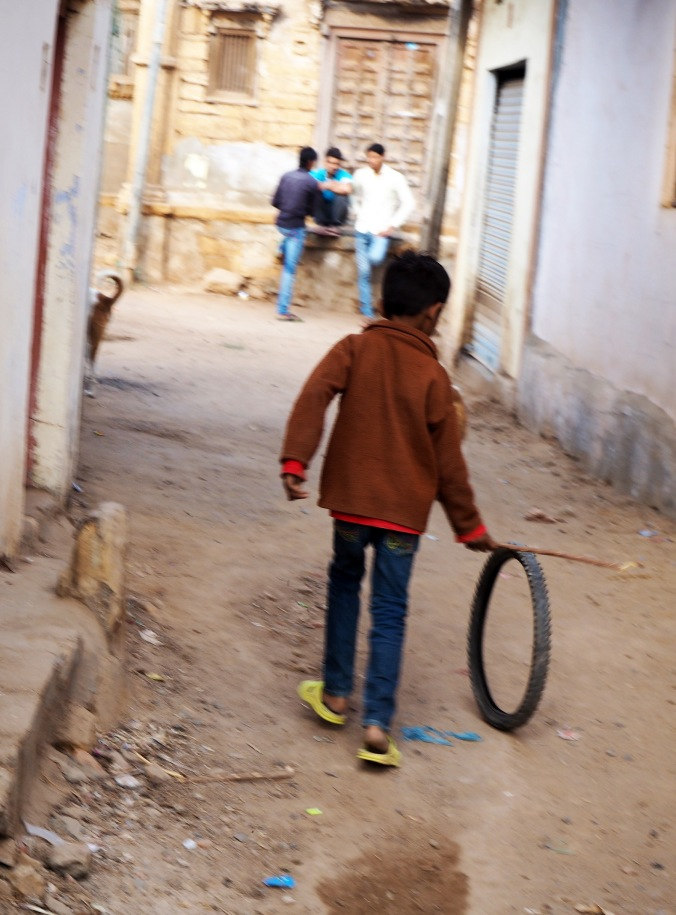 Young boy with old toy in village lane