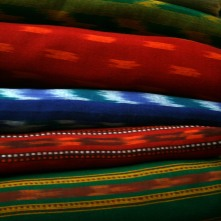 Stacks of hand woven ikat and mashroo fabrics in Ahmedabad