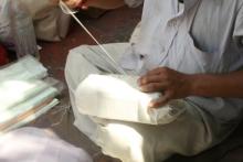 Parcel wallah sewing up parcel, Ahmedabad